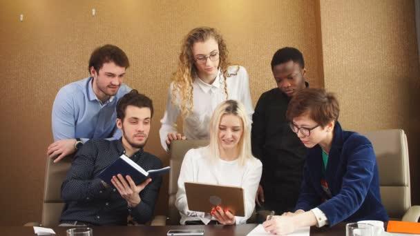 Szőke lány mutatja őt üzleti terv, a munkatársak