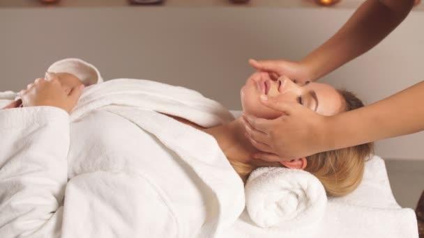 Talentovaný masér dávat masáž obličeje nádherná klientovi.