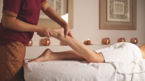 Female therapist reliefs womans pain in legs.