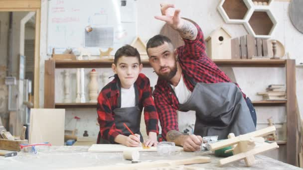 Carpenter pointing at something and little son looks at it at workshop