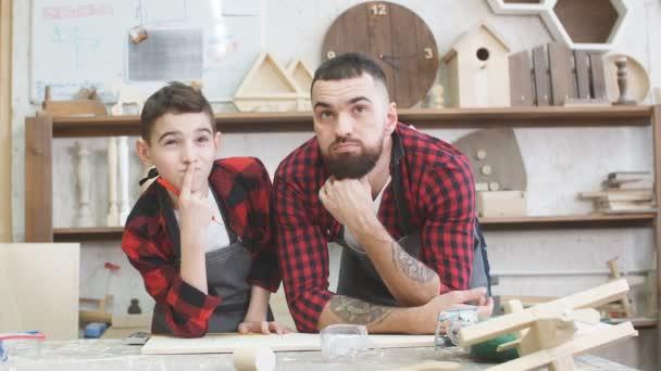 Otec a malý syn dává vysoké pět při návštěvě Dřevoobráběcí masterclass.