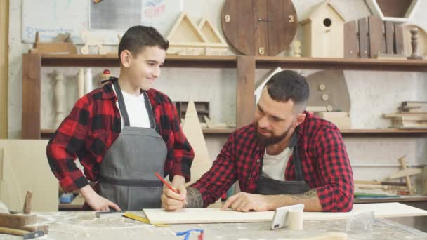 Dad showing video on laptop to his son before working with wood together