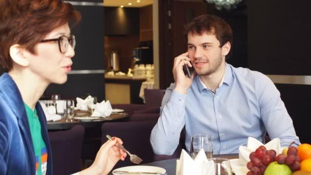 Příjemný pár na oběd a zahájit telefonní hovor v kavárně