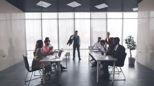 Vůdce týmu zobrazující jeho biceps, zatímco kolegové jsou tleskají mu.