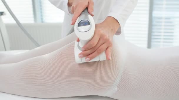 Young brunette female therapist doing beauty therapy against cellulite with LPG machine on woman buttocks in health and wellness medical clinic. LPG massage for lifting body