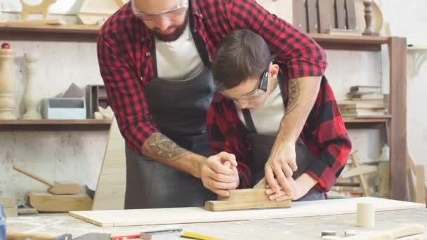 Tesař, sledovat jeho malý čekatel spolupracujícímu tesařských na dřevěný stůl
