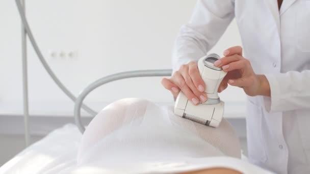 Giovane femmina terapista che fa terapia di bellezza con macchina GPL in clinica medica.
