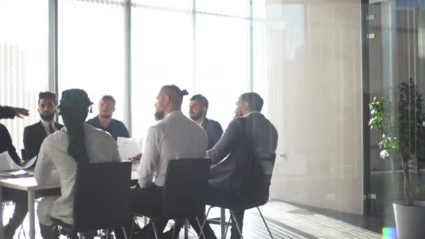 Multiracial male business executives discuss project sitting at conference table