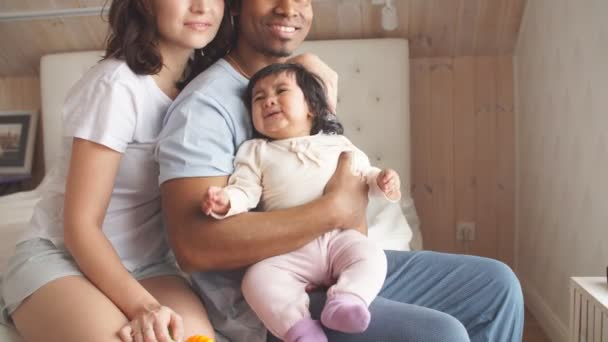 Pleasant mixed race couple taking care of their child