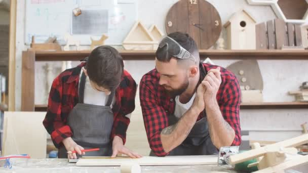 Little boy helps his carpenter father measuring the wooden plank in workshop.