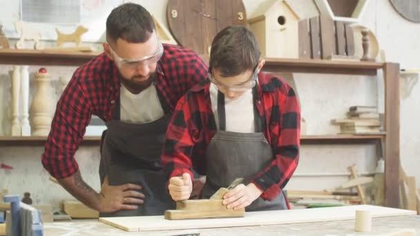 Tesař, malý učeň nebo žák v bezpečnostních brýlí pomocí roviny při práci
