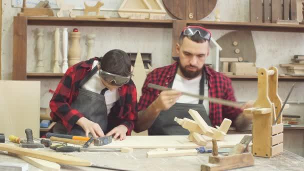 Muž učitel a jeho mužské žák dělat ručně Diy dřevěné hračky