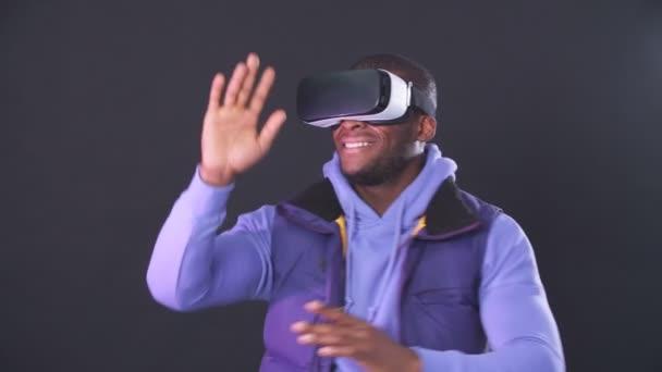Virtual Reality Spiel. Afrikanisch-amerikanischer Mann bedient sich mit Vergnügen eines Head-mounted Displays