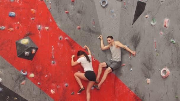 Muscular man helping his girlfriend at climbing wall.