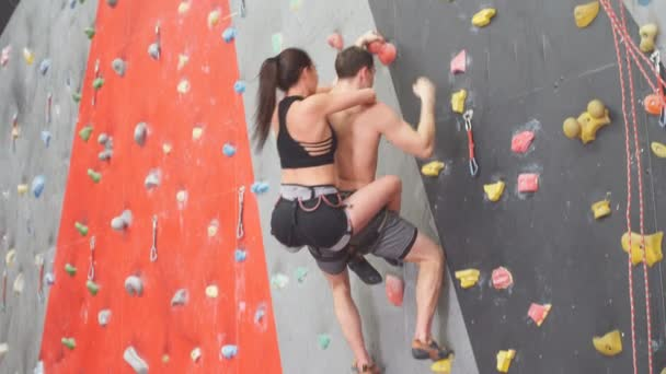 atlet chlap nosit ženu na zádech, zatímco lezení ve sportovním centru