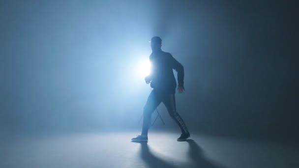Sportos, modern style hip-hop táncos jeleníti meg a dance studio kék háttér, lassú mozgás.