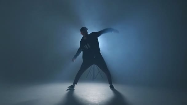 Giovane ballerina danza funky hip hop su sfondo blu al neon di studio isolato, rallentatore