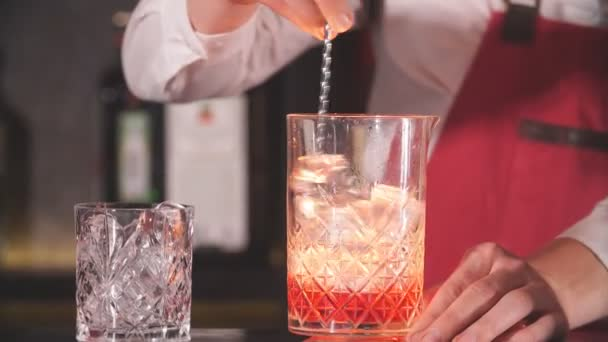 Bartender using long metal spoon to mix ice cubes with drink in a glass