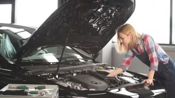 motorok trendfigyelése. aranyos szőke tanul megjavítani az autót