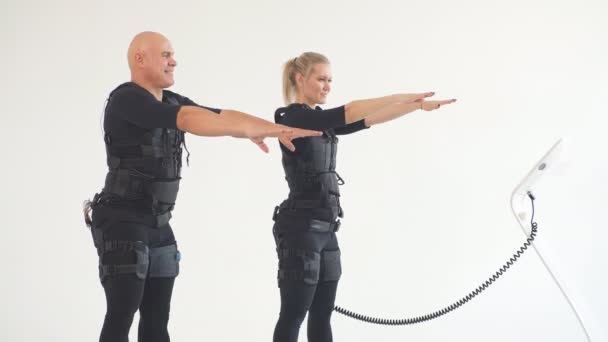 Man and woman in EMS suits developing core strength