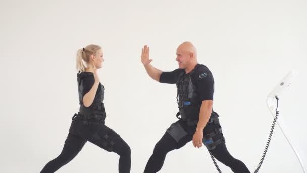 Veselý pár s oblečením do EMS s vysokým pěti během tréninku