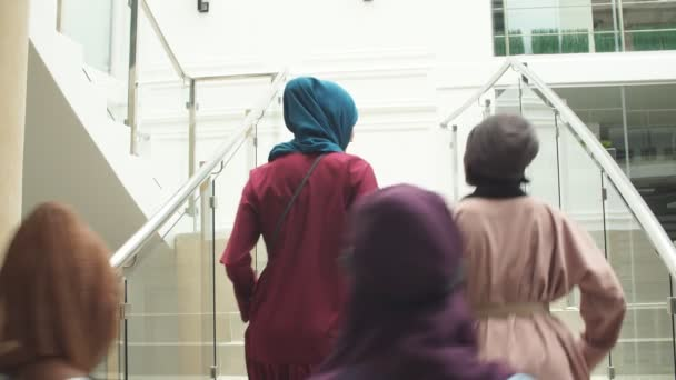 Group of four muslim girls walking at stairs of shopping mall