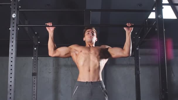 Fitness man pumping up lats muscles, exercising wide-grip pull-up with weight
