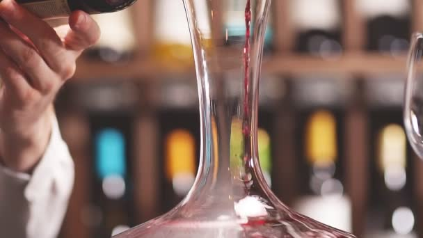 Sommelier esperto che versa vino dal bicchiere da vino decanter ino.