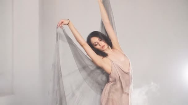 Modern style ballet dancer ex on a studio grey background in fog