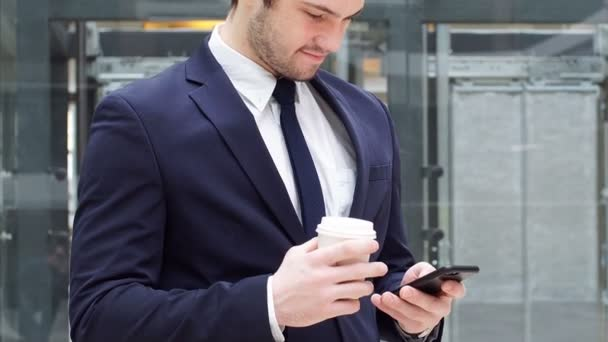 Young confident businessman drinking takeaway coffee and use smartphone.