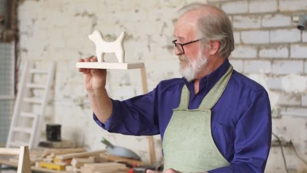 Starý tesař dokončil provádění dřevěných hraček.