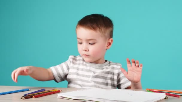 Young talented boy draws a pencil drawing in album on blue background.