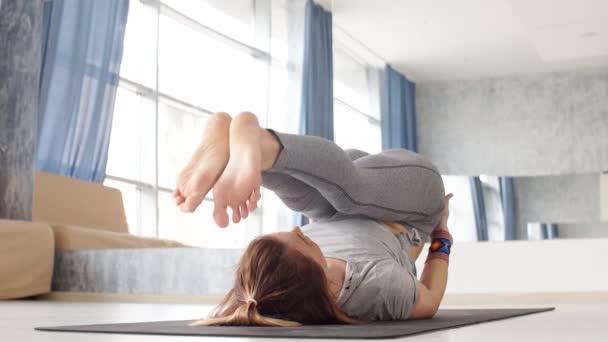 Sportos fiatal nő jóga gyakorlatot végez - az egészséges élet fogalma és a test és a mentális fejlődés közötti természetes egyensúly.
