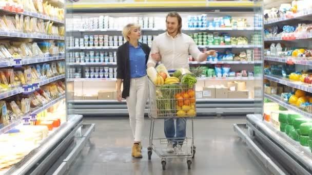 Pár v supermarketu nakupování s nákupním vozíkem nákup potravin