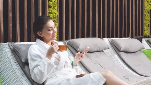 Nice young black-haired girl lying on a sun lounger in Spa salon and surfing the Net.