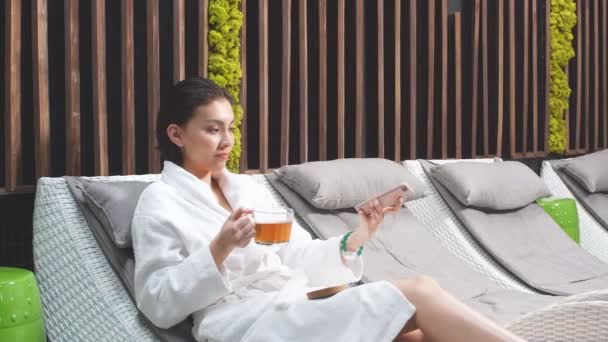 Cheerful young woman in a white robe taking pictures of herself lying on a chaise longue in a modern Spa