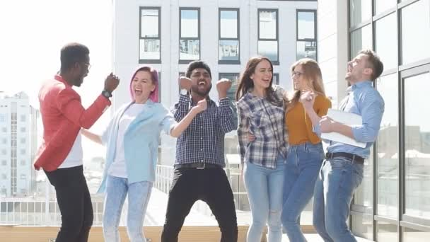 Group of multi ethnic young colleagues celebrates success on terrace of modern office
