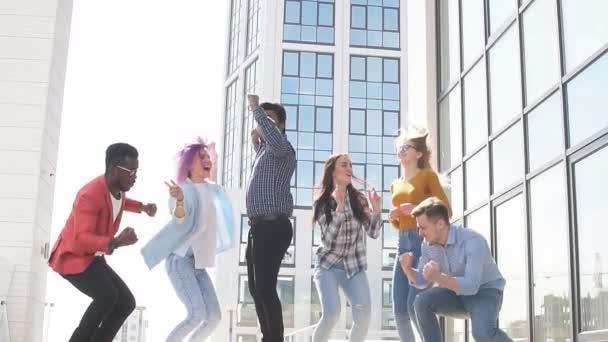 Genç işadamlarından oluşan çok ırklı grup dans ederek ve çatıya atlayarak başarılı bir anlaşmayı kutluyor