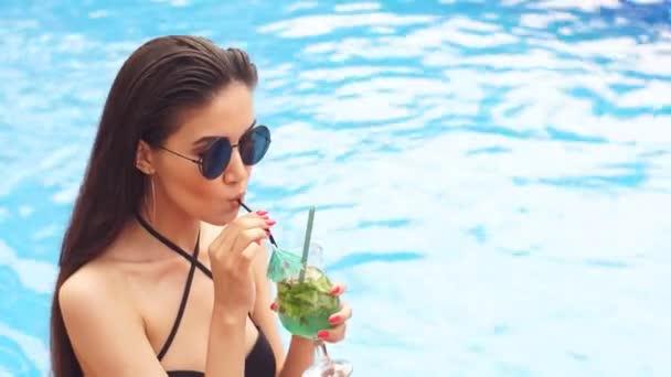 Glamour lány divatos fürdőruhában és napszemüvegben fekszik a medence mellett koktéllal