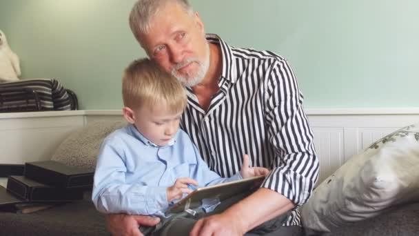 verträumter Opa umarmt beim Spielen auf dem Tablet eines Enkels