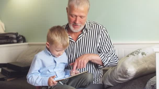 Beautiful grandpa playing with his grandson on the tablet