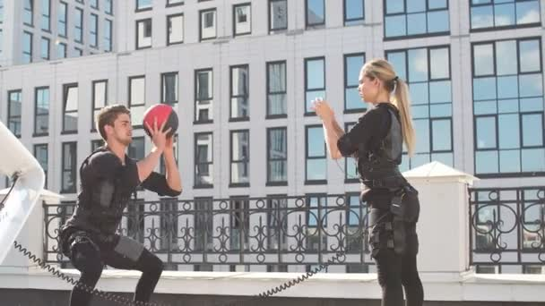 EMS training in the open air. Handsome guy in EMS vest throwing a ball to a beautiful girl