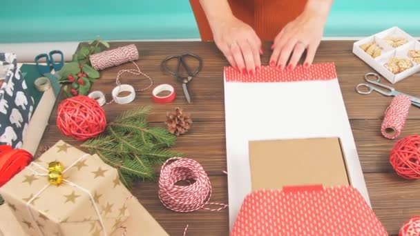 Female hands wrapping Christmas gift in craft ecological paper on dark wooden background with decorating elements.