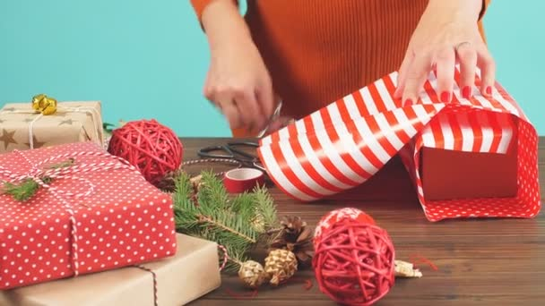 Womans hands tying christmas holiday handmade present in craft paper with twine ribbon.