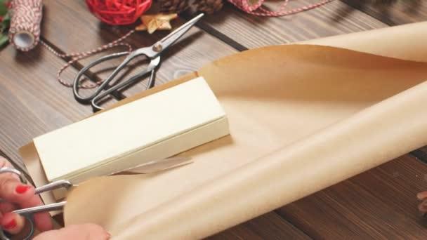 Árukapcsolás piros szalaggal meghajolt a díszdobozban, női kezek kézműves papír csomagolva