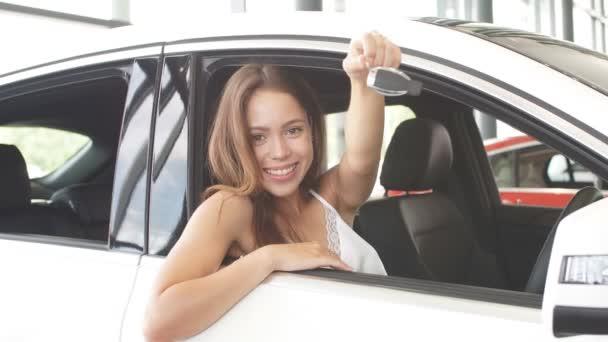 Happy kavkazské mladá řidička sedí v bílém autě ukazuje klíče od auta v showroomu auto
