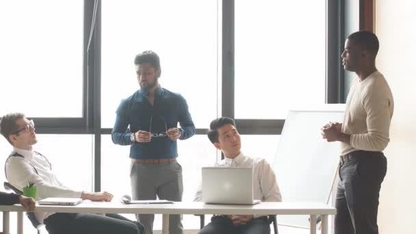 Das multiethnische Männerteam einer modernen Firma kommuniziert in einem modernen Loft-Büro mit Panoramablick