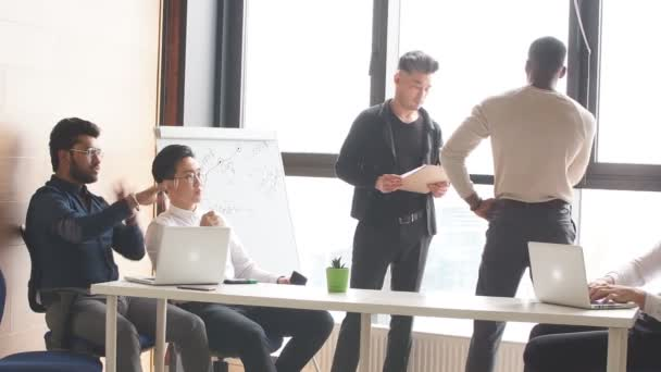 Successful mixed race hipster male team in coworking space