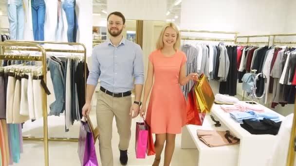 Mladý moderní pár nakupující v obchoďáku s pytlíky v dlaních a dívali se jeden na druhého