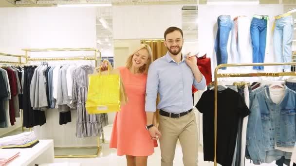 fiatal boldog pár vásárolni együtt ruhákat a divatüzletben. Lassított mozgás.